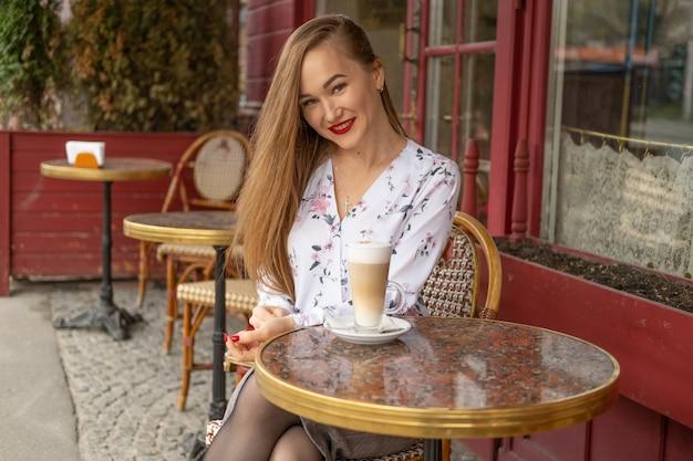 Giovane donna che beve il caffè in un caffè parigino di strada