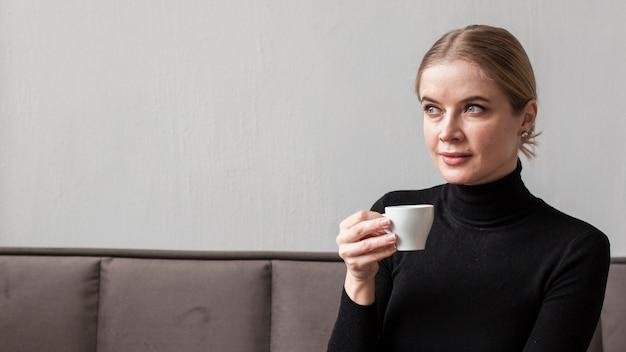 Giovane donna che beve il caffè