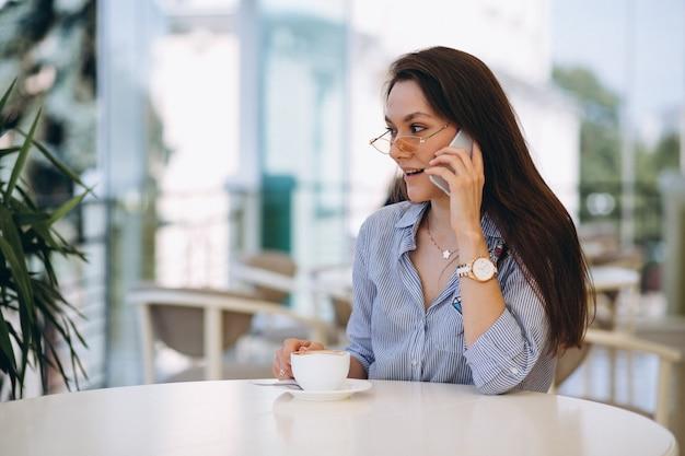 Giovane donna che beve il tè in un caffè