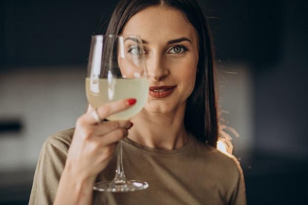 Giovane donna che beve limonata dal vetro in cucina
