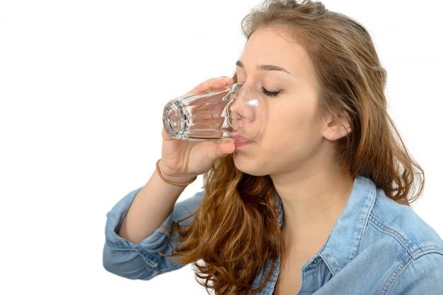 Giovane donna che beve un bicchiere d'acqua, su bianco