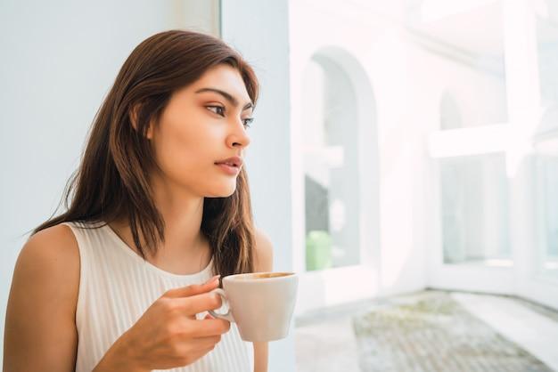 Giovane donna che beve una tazza di caffè alla caffetteria.