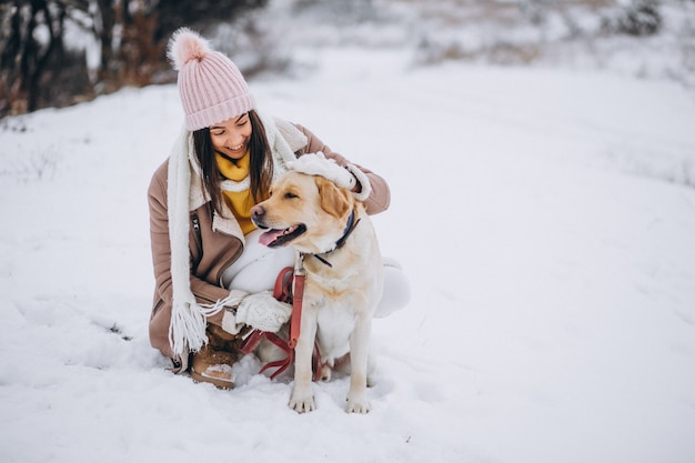 Giovane donna che cammina con il suo cane in un parco di inverno