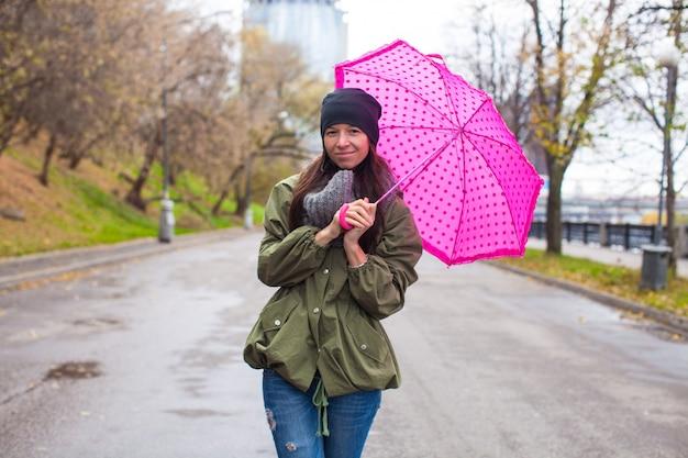 Giovane donna che cammina con l'ombrello nel giorno piovoso di autunno