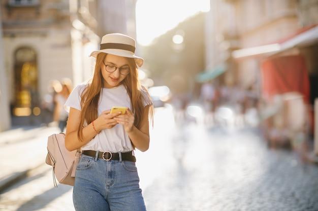 Giovane donna che cammina in città. usando il suo telefono cellulare.
