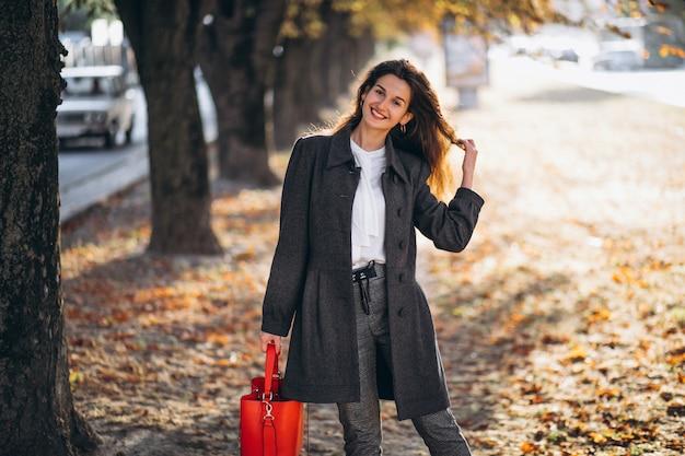 Giovane donna che cammina in un parco di autunno