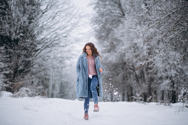Giovane donna che cammina in un parco di inverno