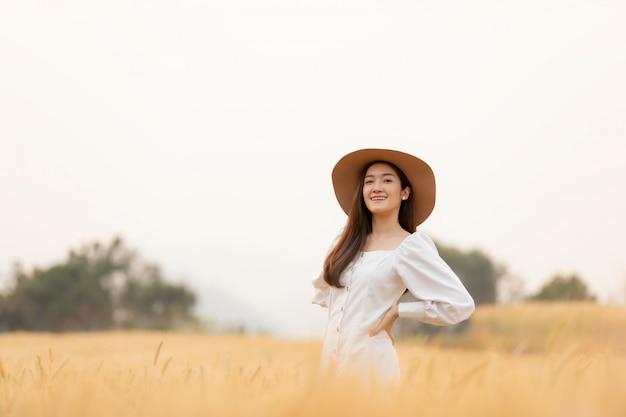 Giovane donna che cammina nel campo dell'orzo con cappello e divertirsi. vacanze estive.