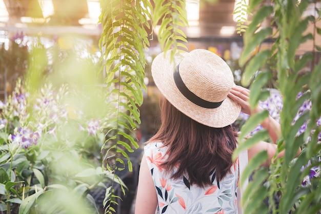 Giovane donna che cammina nel giardino dell'orchidea