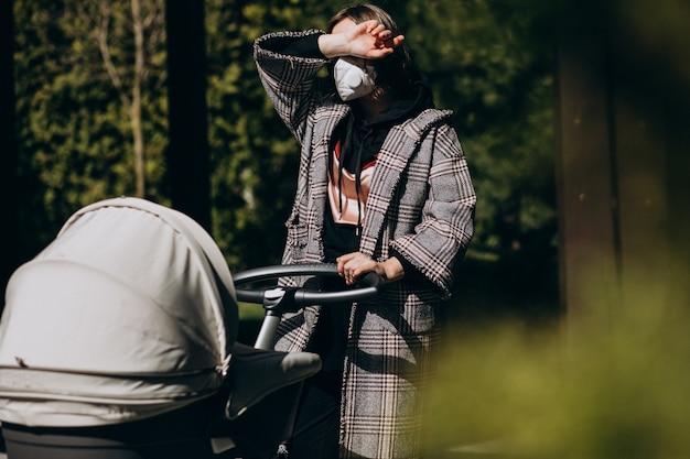 Giovane donna che cammina nella maschera di protezione con carrozzina