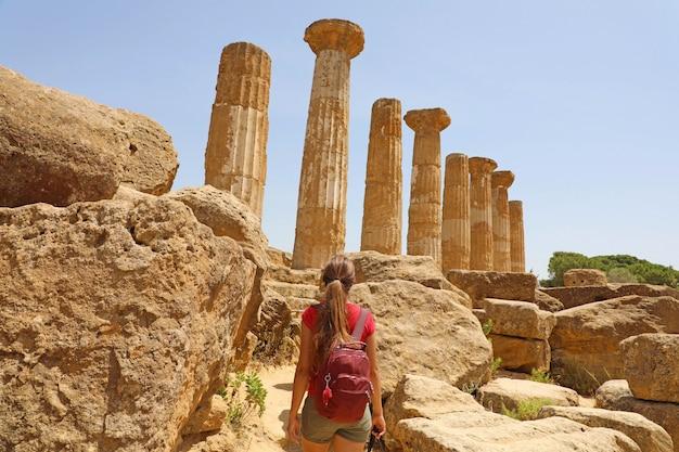 Giovane donna che cammina nella valle dei templi agrigento, sicilia. ragazza viaggiatore visita i templi greci nel sud italia.