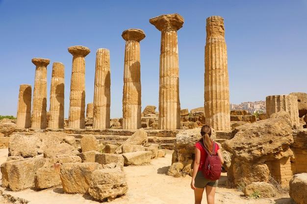 Giovane donna che cammina nella valle dei templi di agrigento, sicilia. ragazza viaggiatore visita i templi greci nel sud italia.