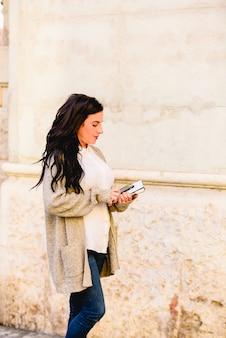 Giovane donna che cammina per la città con i suoi libri e quaderni in braccio