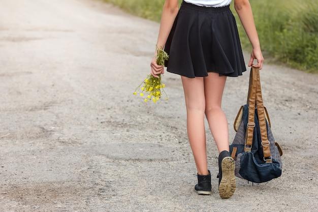Giovane donna che cammina sulla strada con il concetto di viaggio zaino.