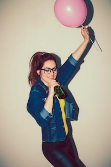 Giovane donna che canta e ballare con un palloncino e una birra