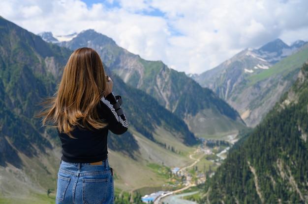 Giovane donna che cattura foto della montagna
