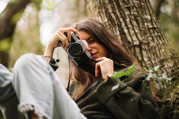 Giovane donna che cattura foto in natura