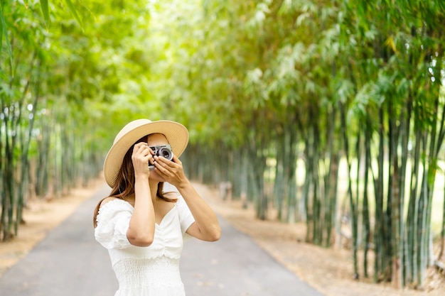 Giovane donna che cattura foto in una foresta di bambù