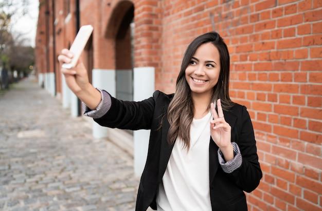 Giovane donna che cattura i selfie con il telefono.