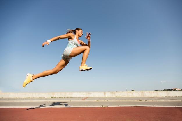 Giovane donna che cattura il salto in lungo