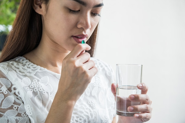 Giovane donna che cattura la pillola della medicina dopo l'ordine del medico
