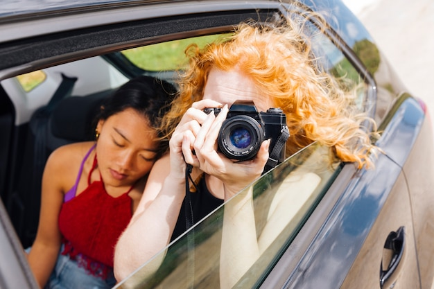 Giovane donna che cattura le maschere sulla macchina fotografica