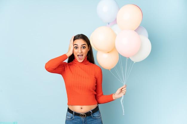 Giovane donna che cattura molti palloni isolati sulla parete blu sorpresa e che indica dito il lato