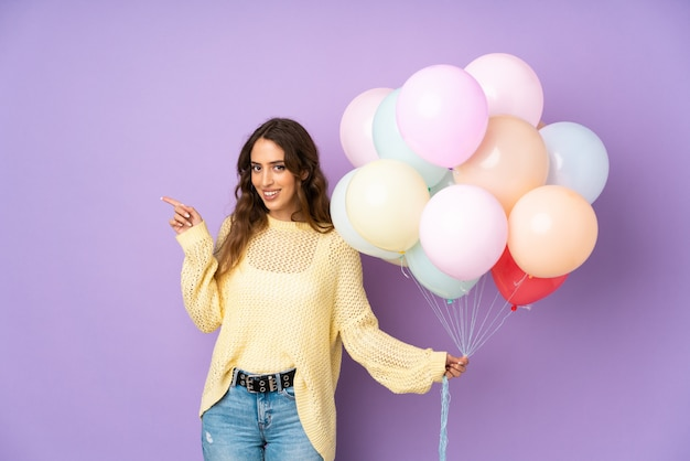 Giovane donna che cattura molti palloni più sul muro viola che punta il dito verso il lato