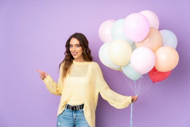 Giovane donna che cattura molti palloni sopra isolato sul muro viola che punta il dito verso il lato