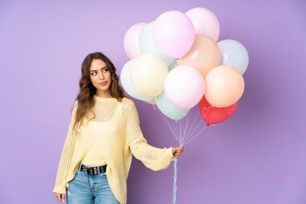 Giovane donna che cattura molti palloni sopra isolato sul muro viola in piedi e guardando al lato