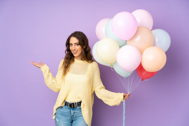 Giovane donna che cattura molti palloni sopra sulla parete porpora che estende le mani al lato