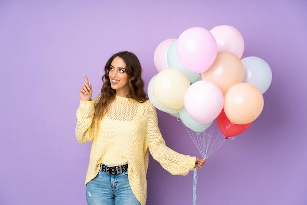 Giovane donna che cattura molti palloni sopra sulla parete porpora che indica con il dito indice una grande idea