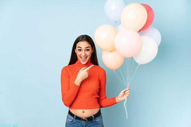 Giovane donna che cattura molti palloni sulla parete blu che punta il dito verso il lato