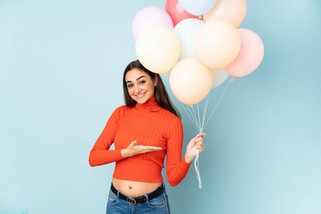 Giovane donna che cattura molti palloni sulle mani blu che si estendono al lato per invitare a venire