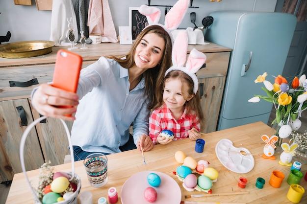 Giovane donna che cattura selfie con la figlia vicino a uova di pasqua