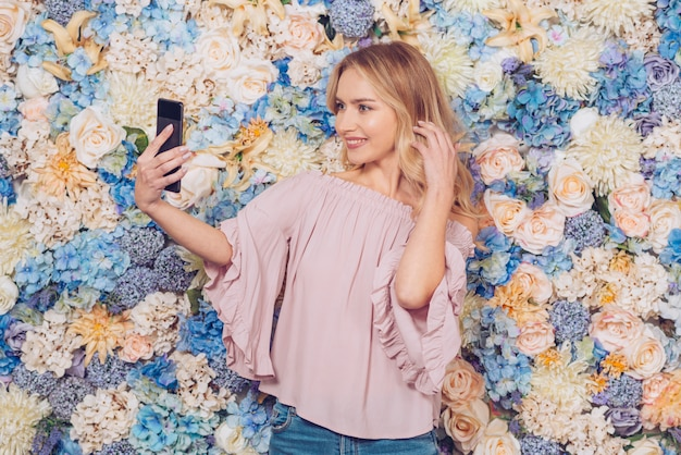 Giovane donna che cattura selfie con smartphone