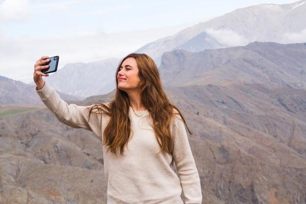 Giovane donna che cattura selfie davanti al paesaggio di montagna