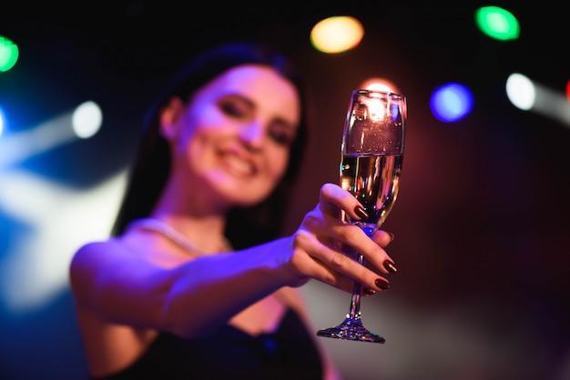 Giovane donna che celebra il vestito nero, con in mano un bicchiere di champagne. festa.