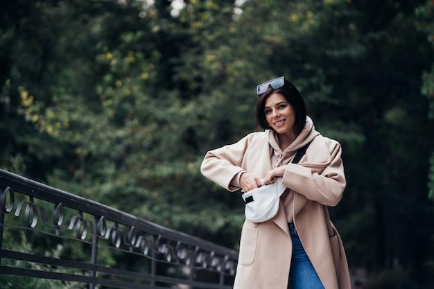 Giovane donna che cerca qualcosa nella sua borsa durante la passeggiata