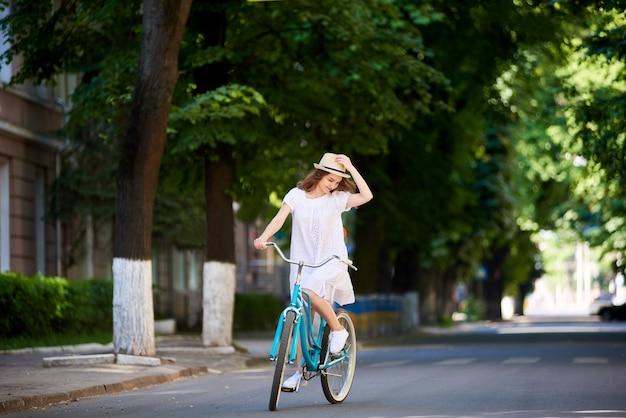 Giovane donna che cicla nella città che registra il suo cappello