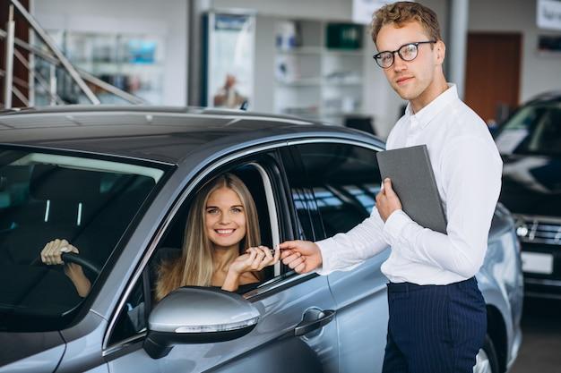 Giovane donna che collauda un'automobile da una sala d'esposizione dell'automobile