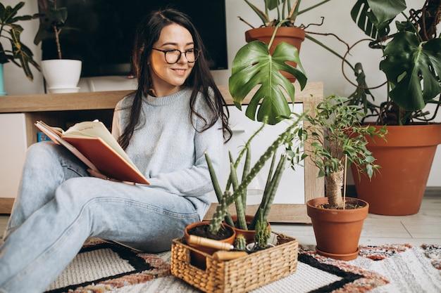 Giovane donna che coltiva le piante a casa