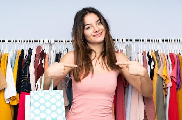 Giovane donna che compra alcuni vestiti in un negozio fiero e soddisfatto di sé