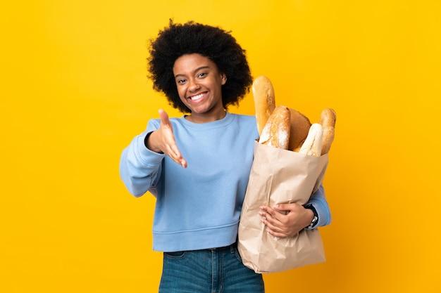 Giovane donna che compra qualcosa di pane isolato su giallo stringere la mano per chiudere un buon affare