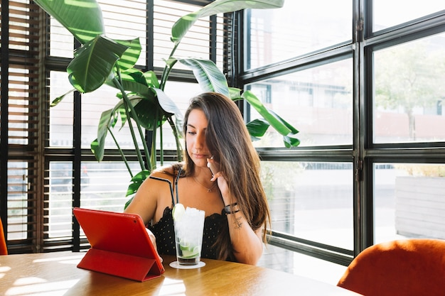 Giovane donna che comunica sul cellulare utilizzando la tavoletta digitale con cocktail sul tavolo