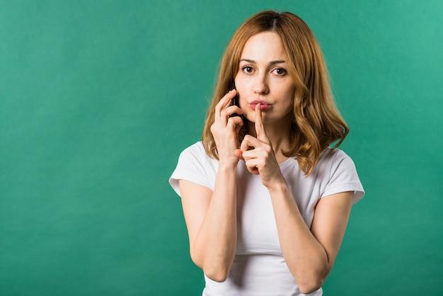 Giovane donna che comunica sul telefono cellulare che fa gesto di silenzio su sfondo verde