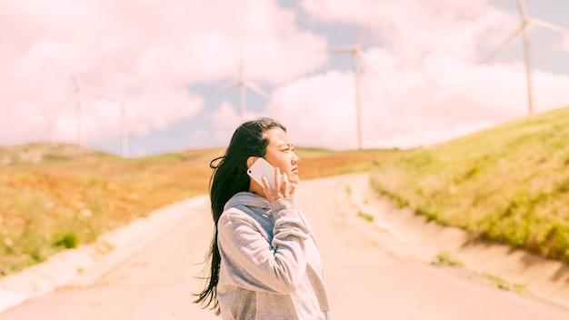 Giovane donna che comunica sul telefono sulla strada campestre