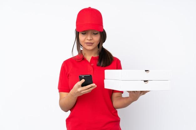 Giovane donna che consegna pizze sul muro bianco isolato inviando un messaggio con il cellulare