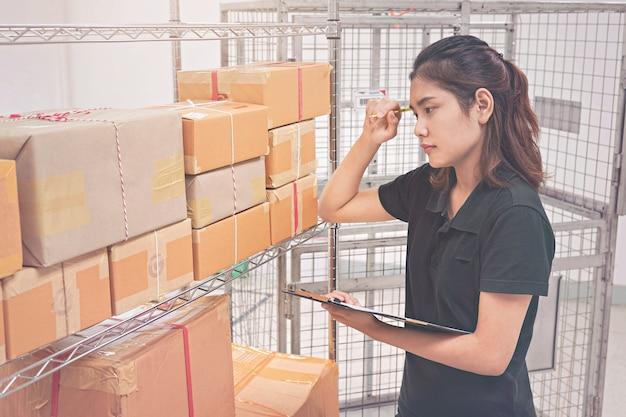 Giovane donna che controlla il pacchetto nel magazzino