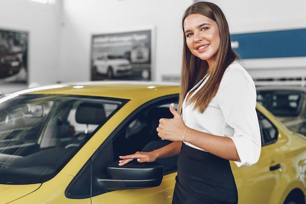 Giovane donna che controlla una nuova macchina che sta per acquistare nel salone dell'auto